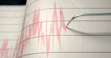 A closeup of a seismograph machine needle drawing a red line on graph paper depicting seismic and eartquake activity - 3D render