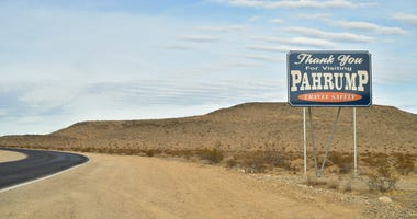 On the outskirts of the town of Pahrump, Nevada stand road signs welcoming visitors and thanking vistors