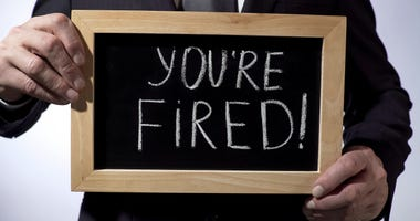 Youre fired with exclamation written on blackboard, businessman holding sign,