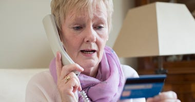 Senior woman giving credit card info over the phone