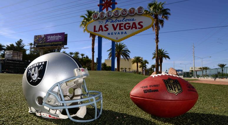 "Shot of Raiders helmet with Las Vegas' ""Welcome"" sign in the background"