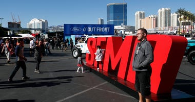 Attendees pose by a SEMA sign at the Las Vegas Convention Center.