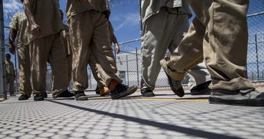 Detainees walk to lunch from one of housing units at the Eloy Detention Center facility in Eloy, Az., on July 28, 2015