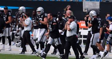 Las Vegas Raiders quarterback Derek Carr (4) and head coach Jon Gruden react after the game at Bank of America Stadium.