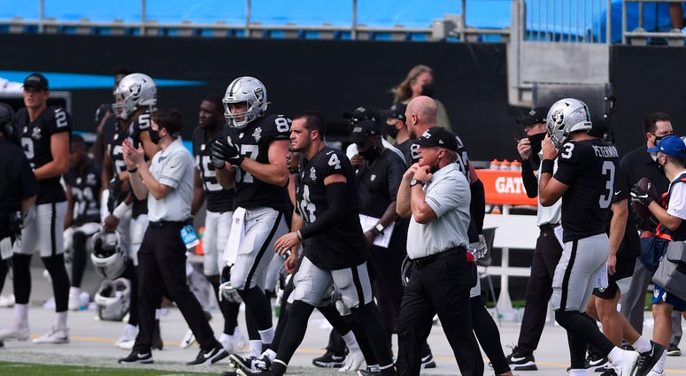 Las Vegas Raiders quarterback Derek Carr (4) and head coach Jon Gruden react after the game at Bank of America Stadium.