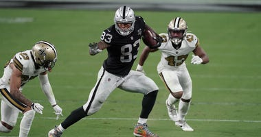 Las Vegas Raiders tight end Darren Waller (83) runs the ball against New Orleans Saints cornerback Marshon Lattimore (23) and free safety Marcus Williams (43) during the fourth quarter of a NFL game at Allegiant Stadium