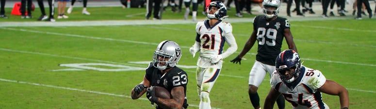 Las Vegas Raiders running back Devontae Booker (23) is pursued by Denver Broncos linebacker Josh Watson (54) on a 23-yard touchdown run in the fourth quarter at Allegiant Stadium.