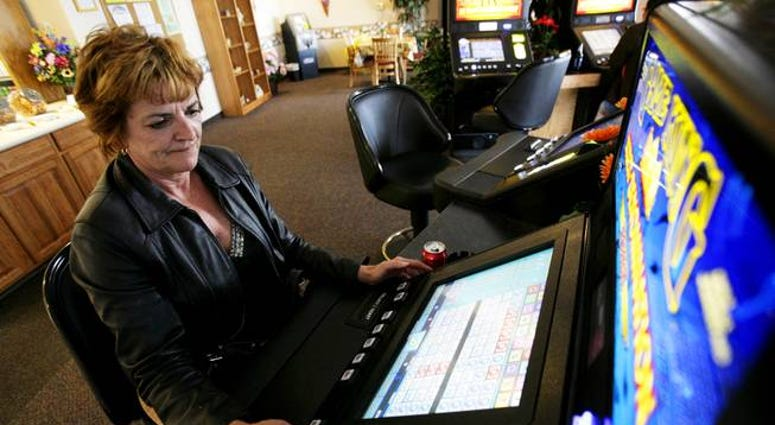 Woman playing a table top video poker machine