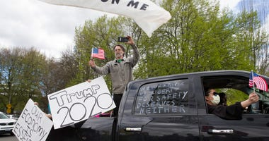 A parade of cars honk horns and show support for President Trump during a 'Hazardous Liberty! Defend the Constitution!' rally to protest the stay-at-home order, at the Capitol building on April 19, 2020 in Olympia, Washington