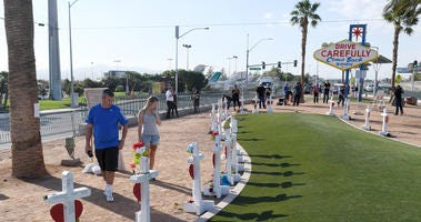 Visitors look at crosses set up for shooting victims behind the Welcome to Fabulous Las Vegas sign on October 1, 2018
