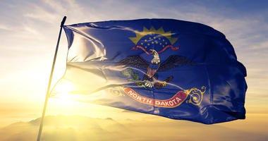 North Dakota state of United States flag on flagpole textile cloth fabric waving on the top sunrise mist fog