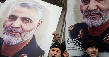 People hold posters showing the portrait of Iranian Revolutionary Guard Major General Qassem Soleimani and chant slogans during a protest outside the U.S. Consulate on January 05, 2020 in Istanbul, Turkey.