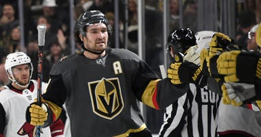 Mark Stone #61 of the Vegas Golden Knights celebrates with teammates on the bench after scoring his second first-period goal against the Arizona Coyotes during their game at T-Mobile Arena