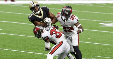 Michael Thomas #13 of the New Orleans Saints is tackled by Jordan Whitehead #33 and Sean Murphy-Bunting #23 of the Tampa Bay Buccaneers