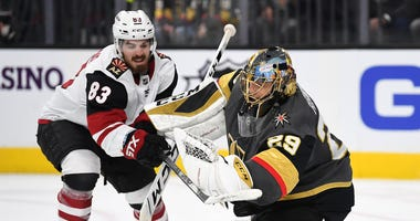 Dec 28, 2019; Las Vegas, Nevada, USA; Arizona Coyotes right wing Conor Garland (83) attempts to chop the puck out of the glove of Vegas Golden Knights goaltender Marc-Andre Fleury (29) during the third period at T-Mobile Arena. Mandatory Credit: Stephen R
