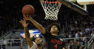 San Diego State Aztecs guard Trey Pulliam (4) drives to the basket ahead of Nevada Wolf Pack guard Nisre Zouzoua (5) at Lawlor Events Center in Reno, Nev.
