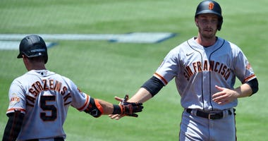 Giants left fielder Austin Slater (13) is greeted by right fielder Mike Yastrzemski (5) after scoring a run during the first inning against the Los Angeles Dodgers at Dodger Stadium.