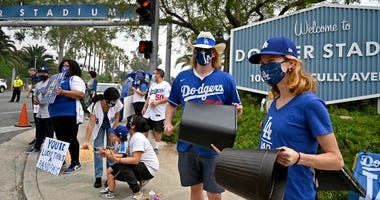 Fans holds signs and bang on trash cans at the front entrance to Dodger Stadium to protest the Houston Astros as they arrive for the game against the Los Angeles Dodgers .
