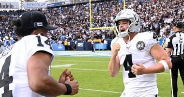 Quarterback Derek Carr #4 is congratulated by quarterback DeShone Kizer #14 of the Oakland Raiders after scoring a touchdown in the game against the Los Angeles Chargers at Dignity Health Sports Park
