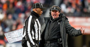 Head coach Jon Gruden of the Oakland Raiders discusses a penalty with a referee during a game against the Denver Broncos at Empower Field at Mile High on December 29, 2019