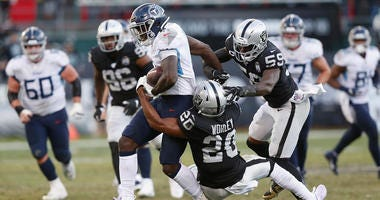 A.J. Brown #11 of the Tennessee Titans is tackled by Daryl Worley #20 and Tahir Whitehead #59 of the Oakland Raiders in the fourth quarter at RingCentral Coliseum on December 08, 2019