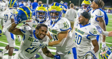 Delaware football players celebrates last week's triple-overtime win at Rhode Island.