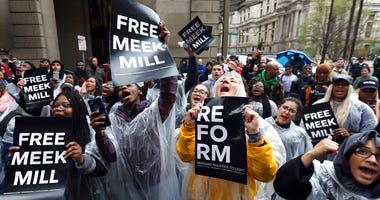 Protesters demonstrate in front of a courthouse during a hearing for rapper Meek Mill.