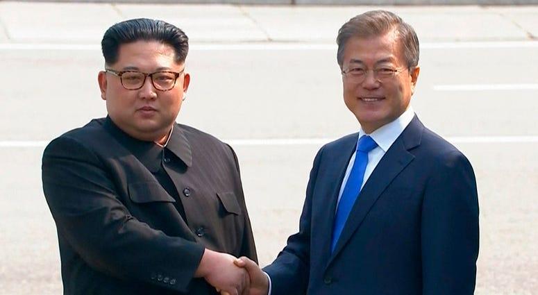 North Korean leader Kim Jong Un, left, shakes hands with South Korean President Moon Jae-in as Kim crossed the border into South Korea.