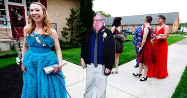Allison Closs arrives for the Carlisle High School senior prom at Letort View Community Center at Carlisle Barracks in Carlise, Pa., with a cutout of actor Danny DeVito.