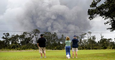 People watch as ash rises from the summit crater of Kilauea volcano.
