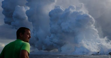 Joe Kekedi watches as lava enters the ocean, generating plumes of steam.