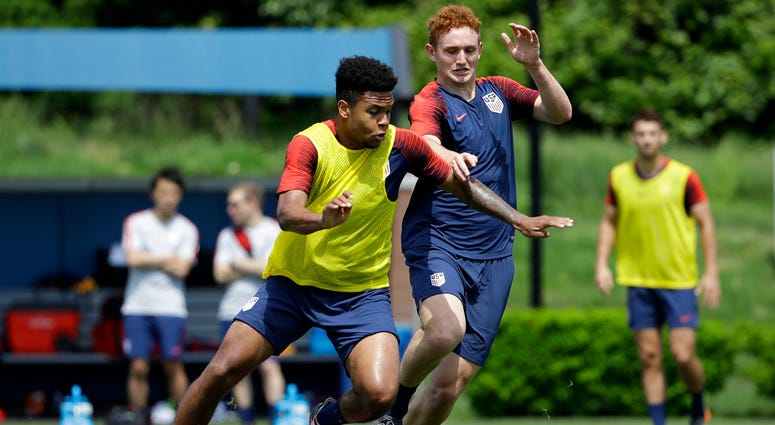 United States' Weston McKennie, left, and Josh Sargent battle for the ball during soccer practice at the University of Pennsylvania.