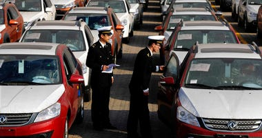 Chinese customs officials inspect cars being loaded for export at a port in Qingdao in eastern China's Shandong province.