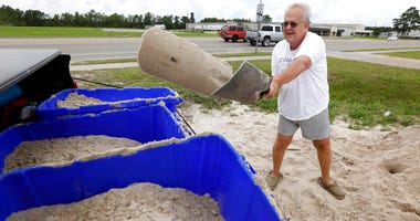 George Estes tosses sand into storage tubs at a Harrison County Road Department sand bagging location.