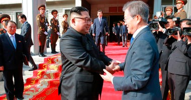 North Korean leader Kim Jong Un, left, and South Korean President Moon Jae-in, right, shake hands after their meeting at the northern side of Panmunjom in North Korea.
