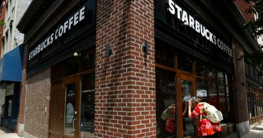 A woman peers into a closed Starbucks Coffee shop.