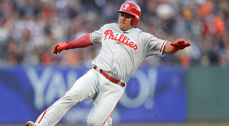 Philadelphia Phillies' Jorge Alfaro slides safely into third base with a triple during the third inning of a baseball game against the San Francisco Giants.