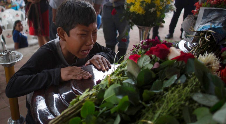 A youth cries over the coffin of Nery Otoniel Gomez Rivas, 17, whose body was pulled from the volcanic ash during the eruption of the Volcan de Fuego, during his wake.