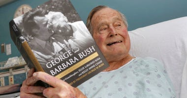 Former President George H.W. Bush sits in his hospital bed while reading a book about himself and his late wife.