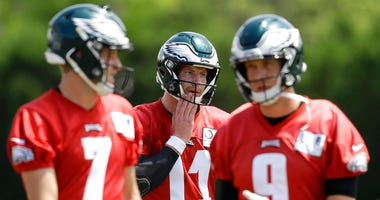 Philadelphia Eagles quaterbacks Carson Wentz (11), Nick Foles (9), and Nate Sudfeld (7) walk to the next drill during practice at the NFL football team's training facility in Philadelphia.