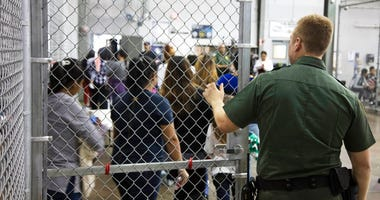 In this photo provided by U.S. Customs and Border Protection, a U.S. Border Patrol agent watches as people who've been taken into custody related to cases of illegal entry into the United States, stand in line at a facility in McAllen, Texas.