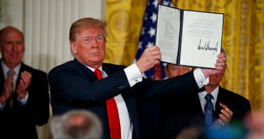 """President Donald Trump shows off a """"Space Policy Directive"""" after signing it during a meeting of the National Space Council in the East Room of the White House."""