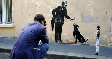 A man takes a picture of a graffiti believed to be attributed to street artist Banksy, in Paris.