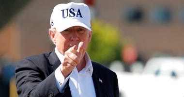 President Donald Trump points before boarding Air Force One at Morristown Municipal Airport, in Morristown, N.J., Sunday, July 8, 2018, en route to Washington from Trump National Golf Club in Bedminster, N.J.