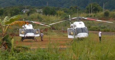 Two helicopters wait near the cave for more evacuations of the boys and their soccer coach who have been trapped since June 23, in Mae Sai, Chiang Rai province, northern Thailand Monday, July 9, 2018.