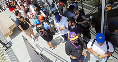 Los Angeles Lakers fans wait in line around noon for promised free pizza that will be handed out between 2 and 5 p.m. at Blaze Pizza, a restaurant chain NBA basketball player LeBron James was an original investor in.