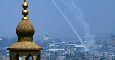 Smoke trails are seen as rockets are launched from the Gaza Strip toward Israel, in Gaza City.