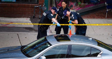 Police investigate a car at the scene of a shooting in Toronto, on Monday, July 23, 2018.