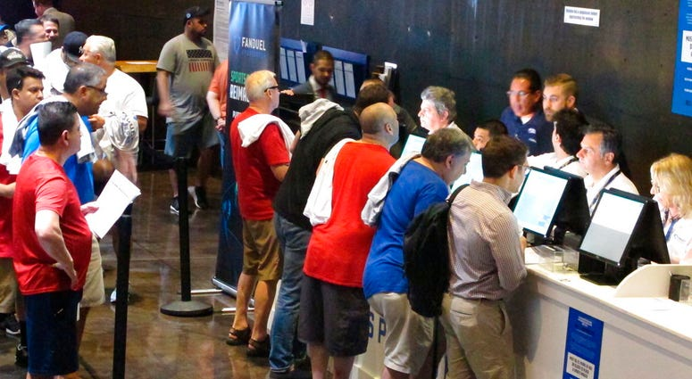 This July 14, 2018, photo shows people placing bets on sporting events at the Meadowlands Racetrack in East Rutherford N.J.