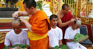 Soccer coach Ekkapol Chantawong, left, and teammates who were rescued last week from a flooded cave have their heads shaved in a traditional Buddhist ceremony in Mae Sai district, Chiang Rai province, northern Thailand, Tuesday, July 24, 2018.